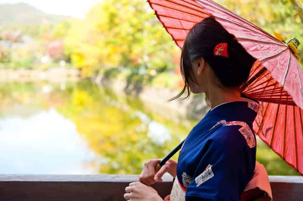 A Japanese woman holding a paper umbrella.