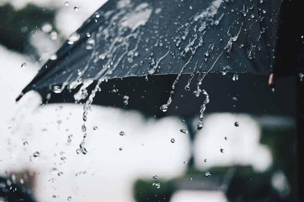 A close look at raindrops falling off a waterproof umbrella.