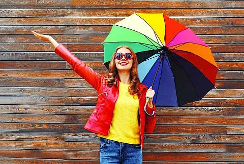 A woman in a colorful outfit holding a rainbow-colored umbrella.