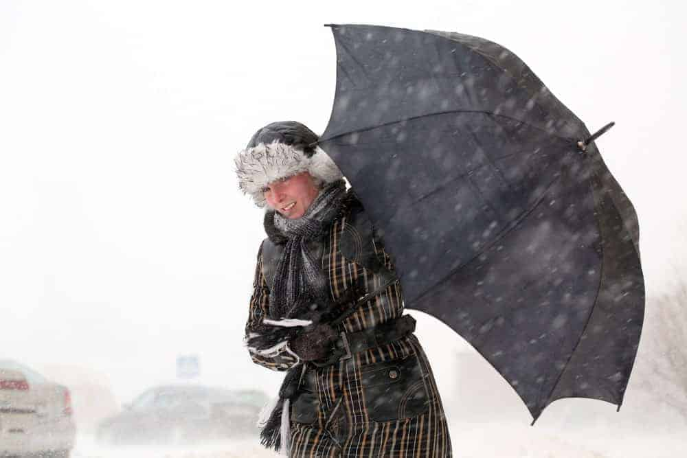 A woman using a high wind umbrella to protect herself from the blizzard.