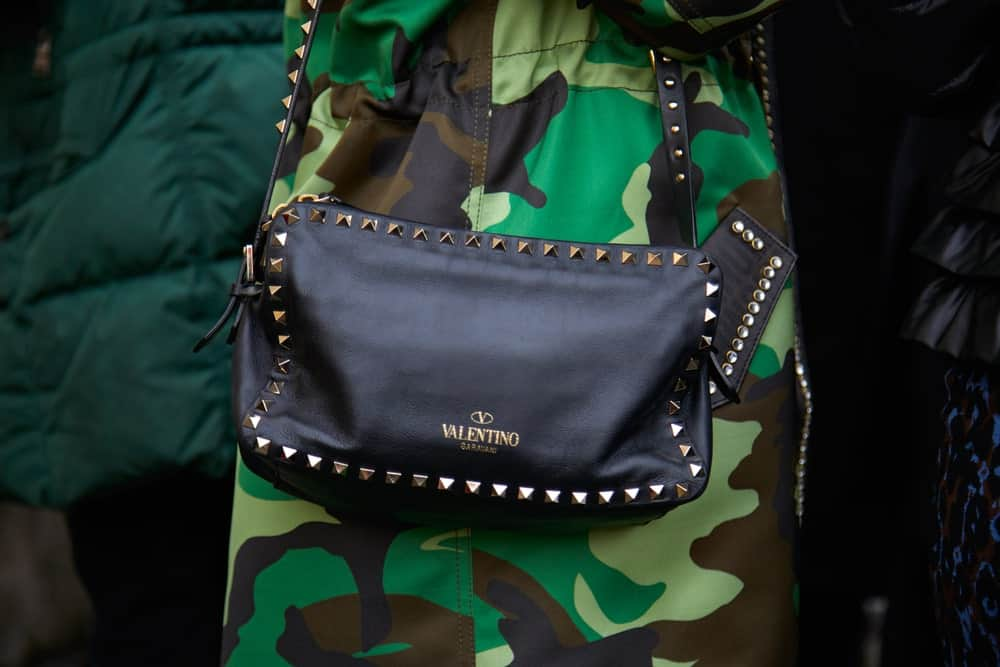 Woman with black leather Valentino bag and green camouflage coat.