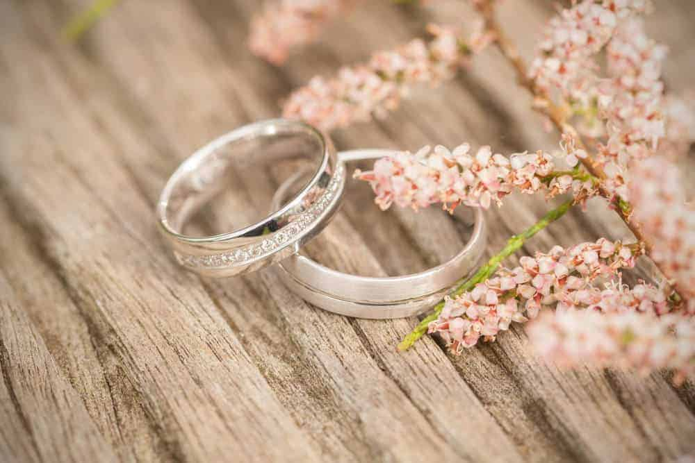 A close look at wedding bands on a wooden table.