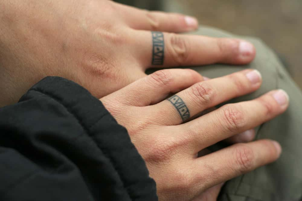 A close look at a couple's hands with tattoo wedding rings.