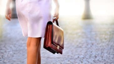A woman heading to work carrying a brown leather portfolio bag.