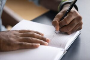Person writing with a pen in a blank book