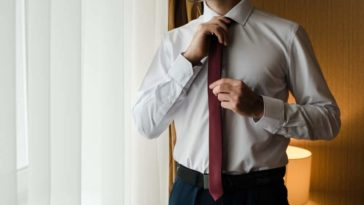 A man wearing a dress shirt without pockets adjusting his necktie.