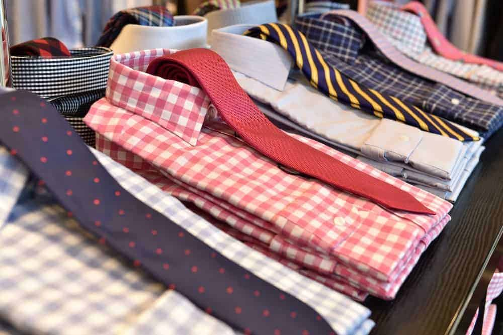 Sets of dress shirts without pockets and neckties on display at a store.