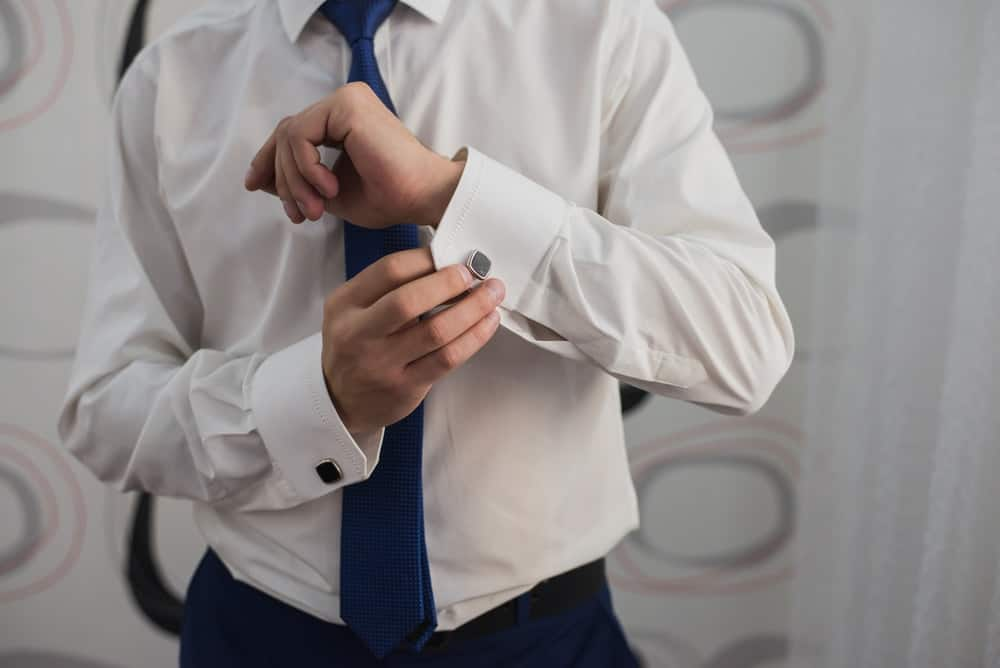 A man putting on cufflinks to his dress shirt without pockets.