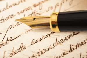 Coit pen resting on a sheet of paper covered in writing