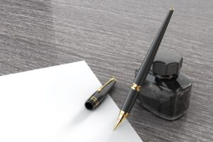 Fountain pen with pot of ink and blank page on a gray background