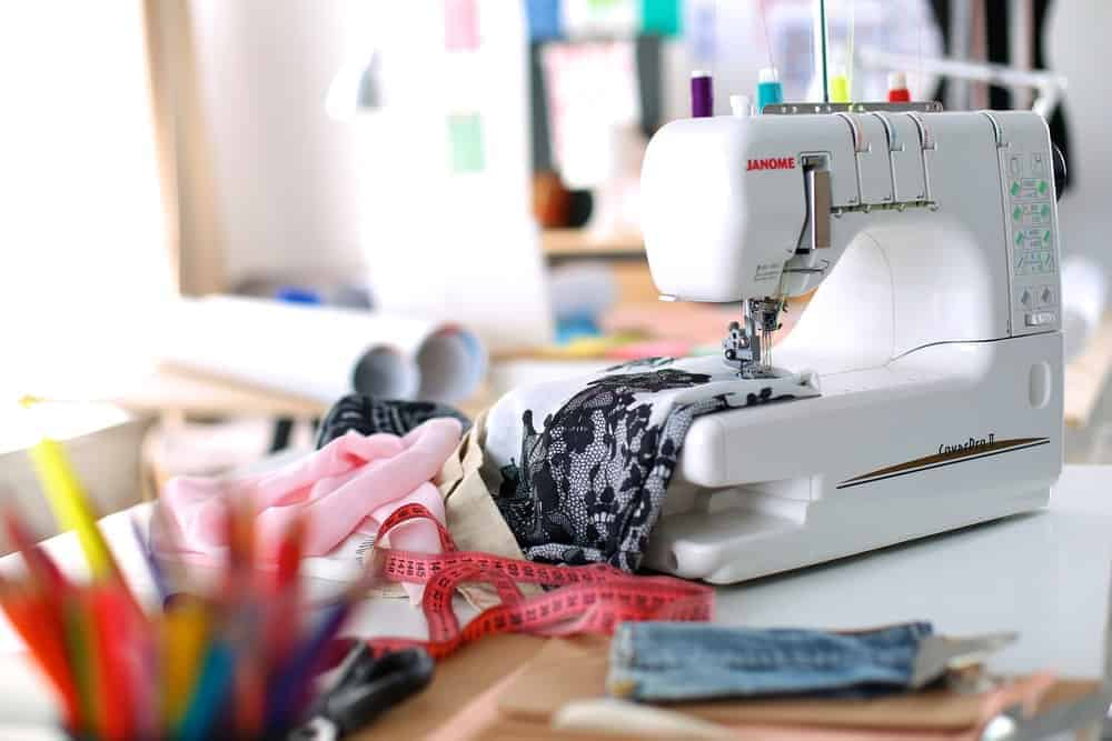 A look at a sewing machine on a work desk along with sewing materials.