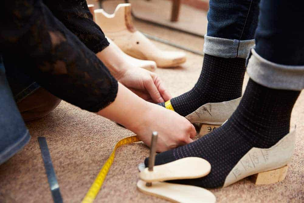 Measuring woman's foot for shoes