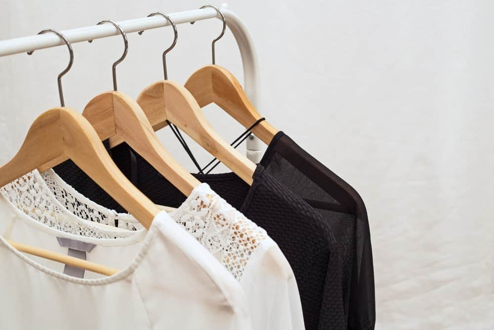A close look at different blouses for women on display on a rack.