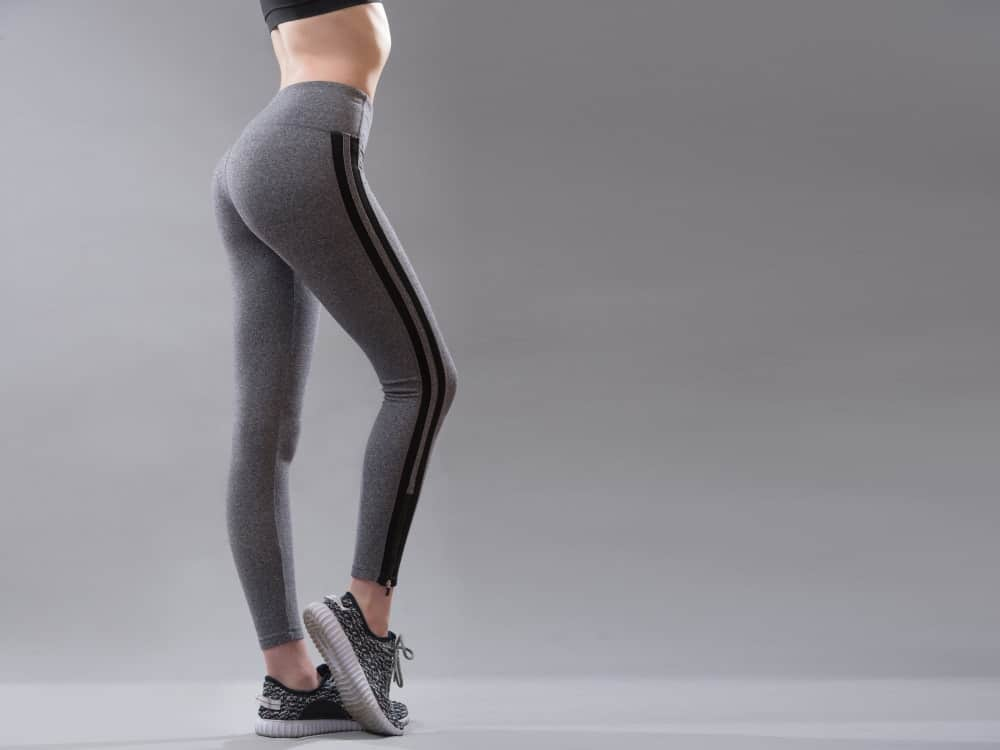 A close look at a woman wearing a pair of sporty gray leggings.