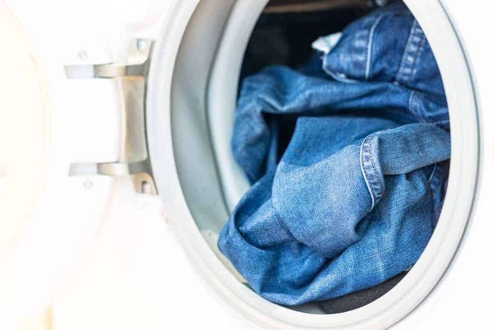 A close look at a pair of jeans inside the washing machine.