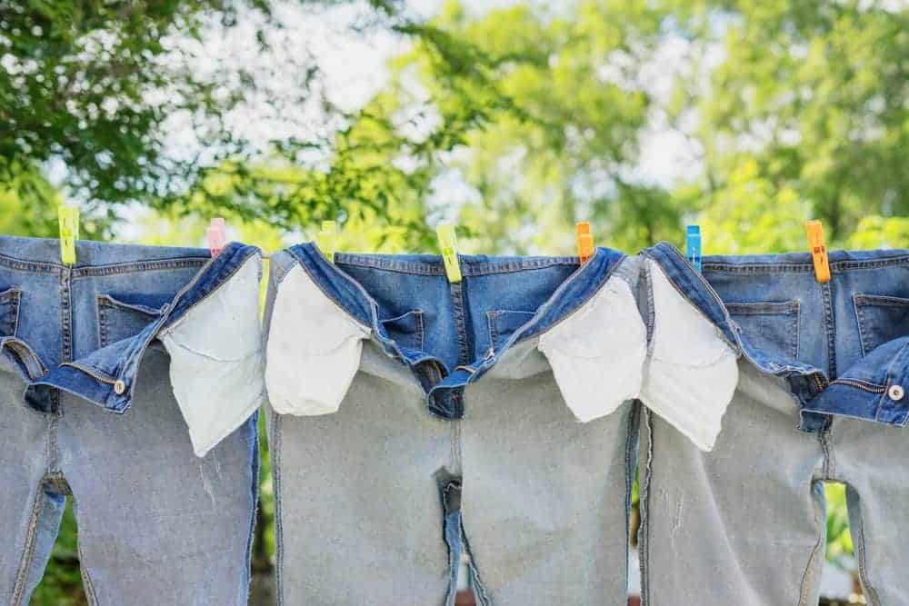 Pairs of inside-out jeans that are hanging on a clothes line.