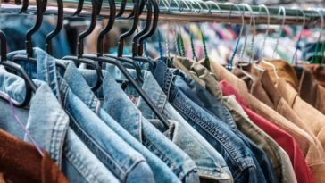 A close look at a rack of used clothes on display at a store.