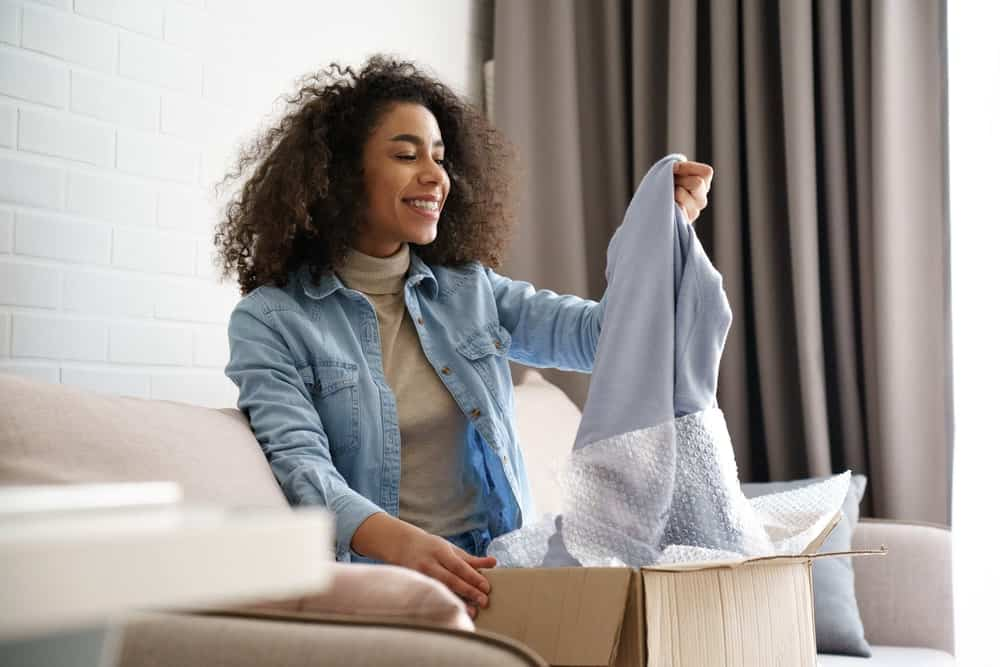 A woman inspecting the clothes she ordered online.
