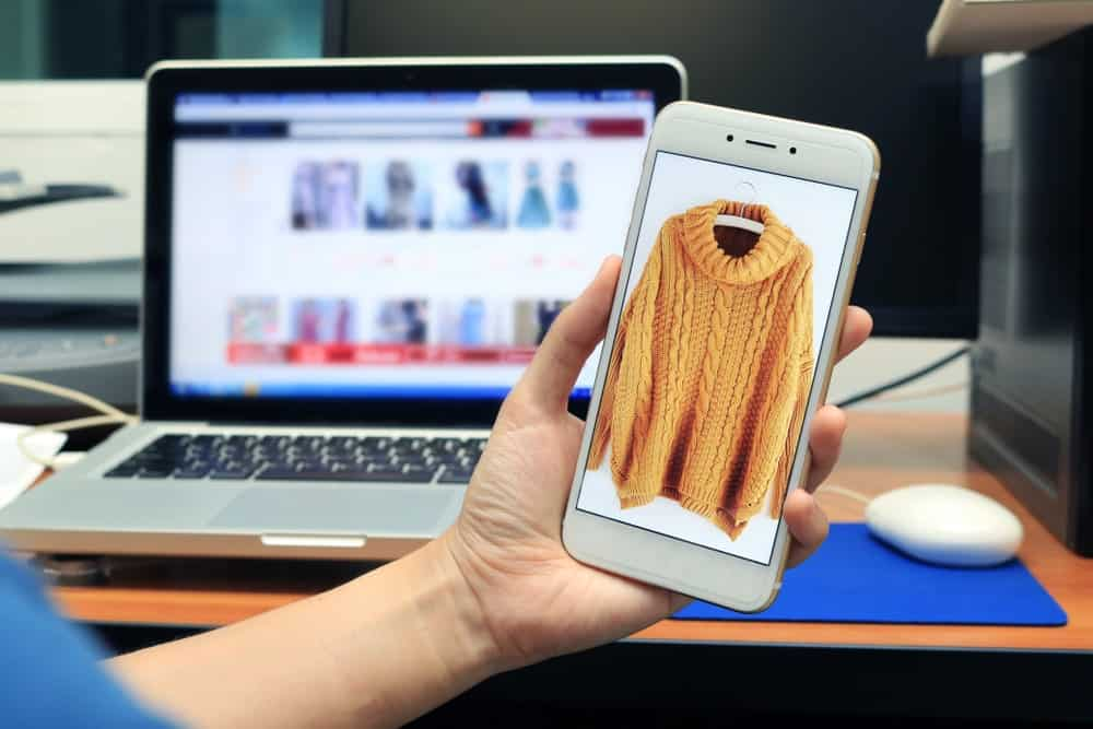 A mobile phone showcasing the sweater for sale in an online shop.