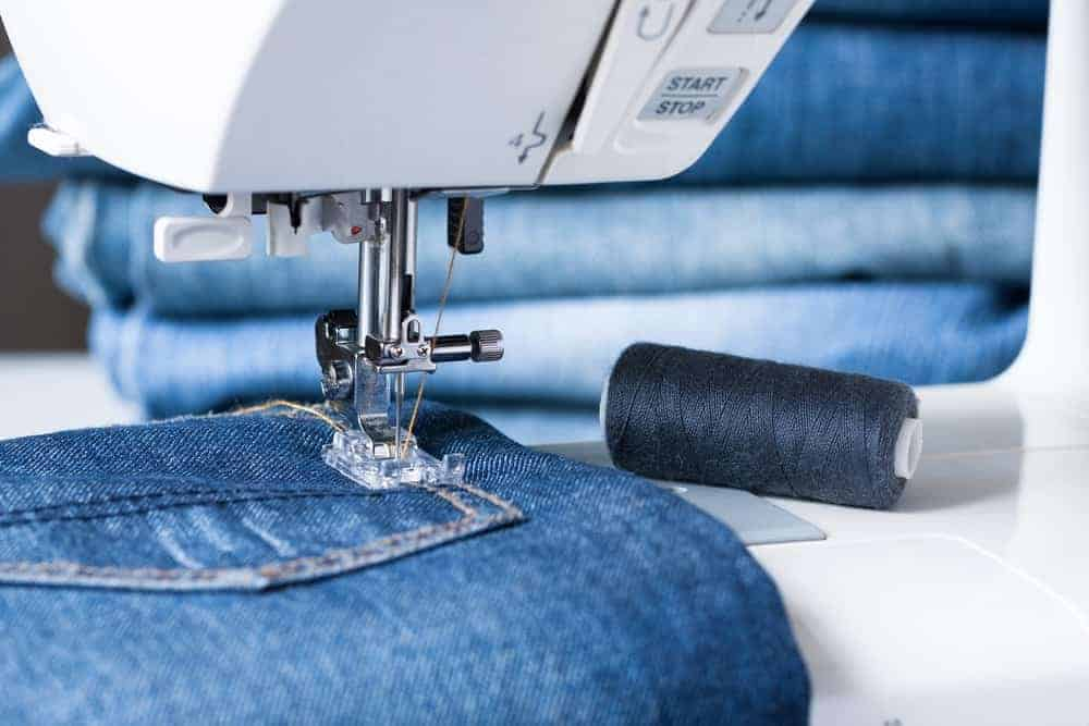 A close look at a pair of jeans being sewn with a machine.