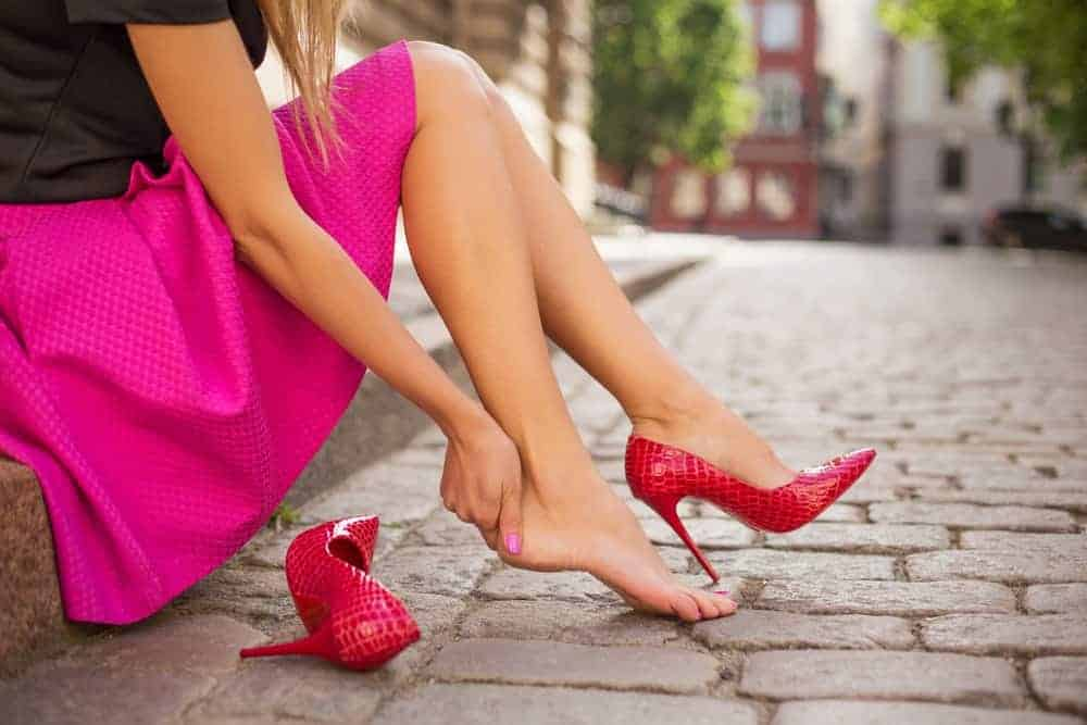 A woman wearing a pair of high heels caressing her ankle.