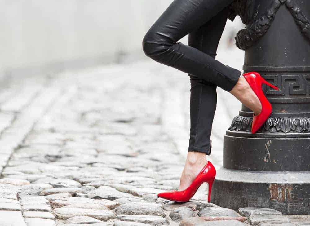 A woman wearing a pair of red high-heeled shoes with her black leather pants.