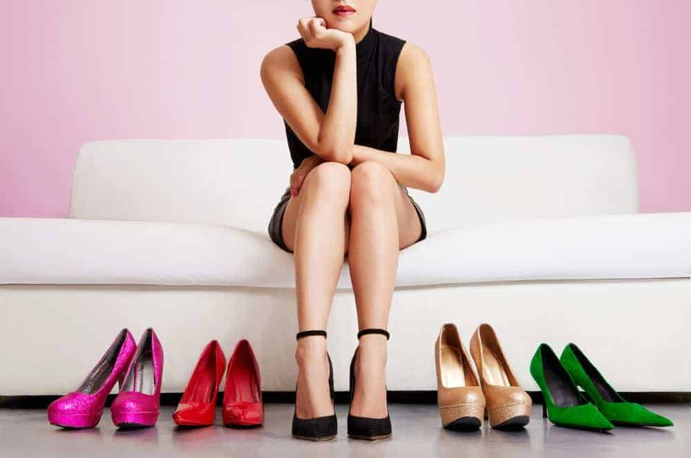 A woman sitting on a couch choosing which high-heeled shoes to wear.