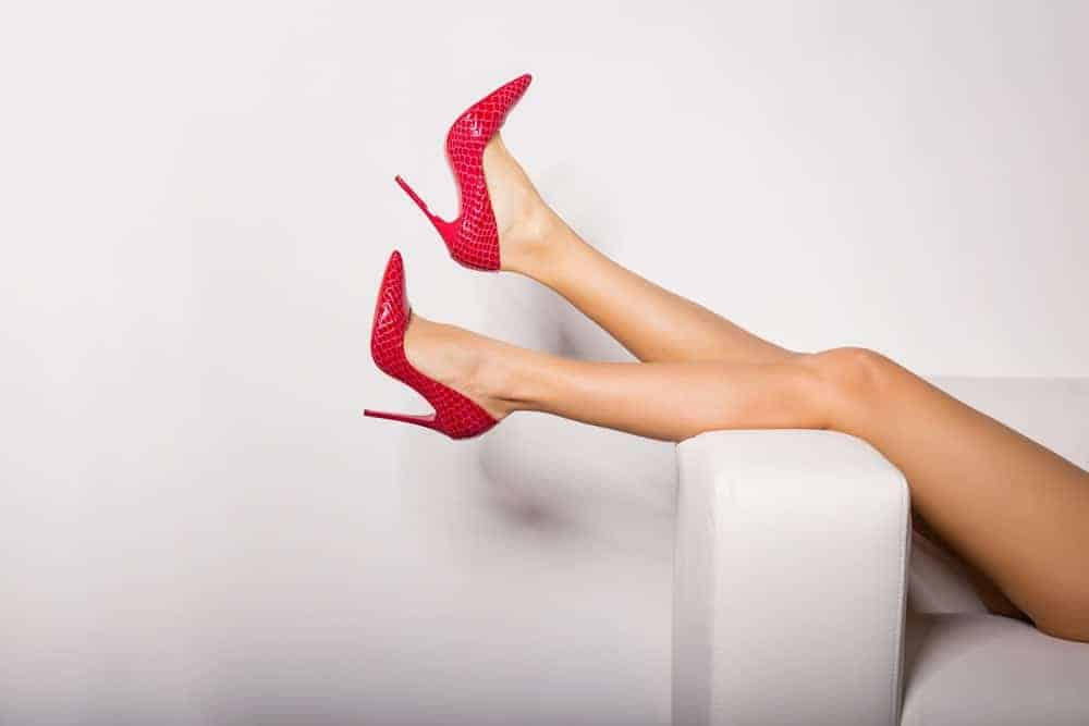 A woman wearing a pair of red high-heeled shoes laying down on a couch.
