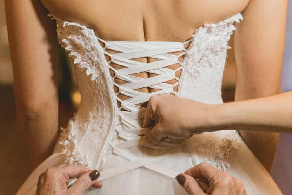 A bride being assisted into her corset.