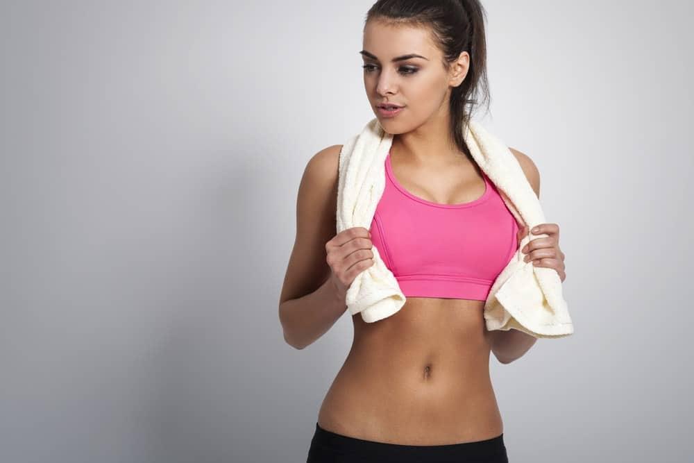 A woman wearing a bright pink sports bra post workout.