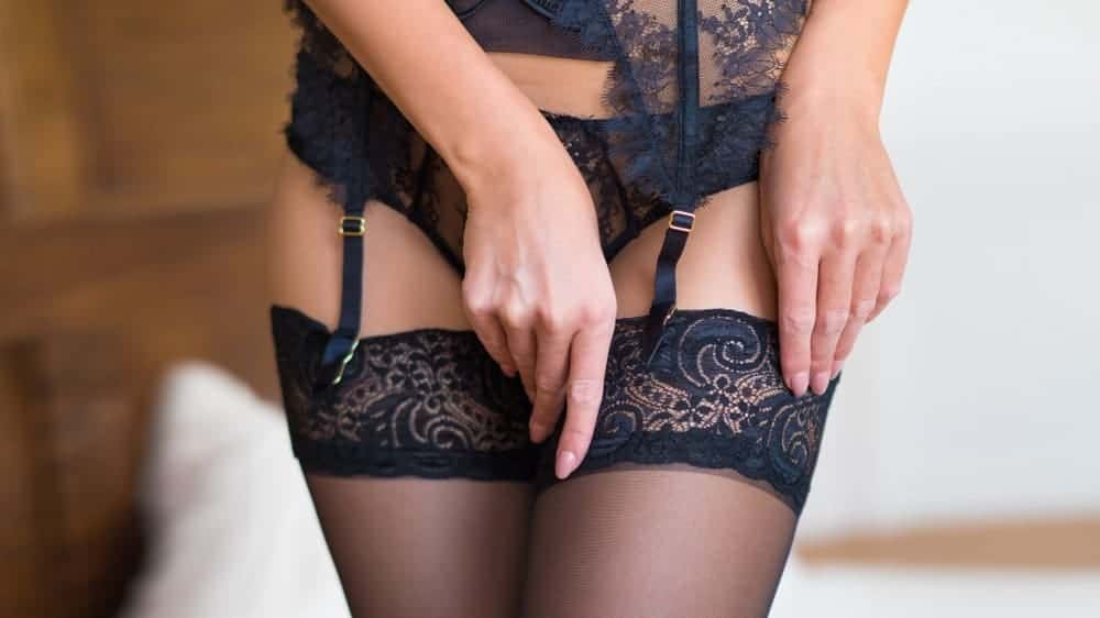 This is a close look at a woman wearing a lace garter belt.