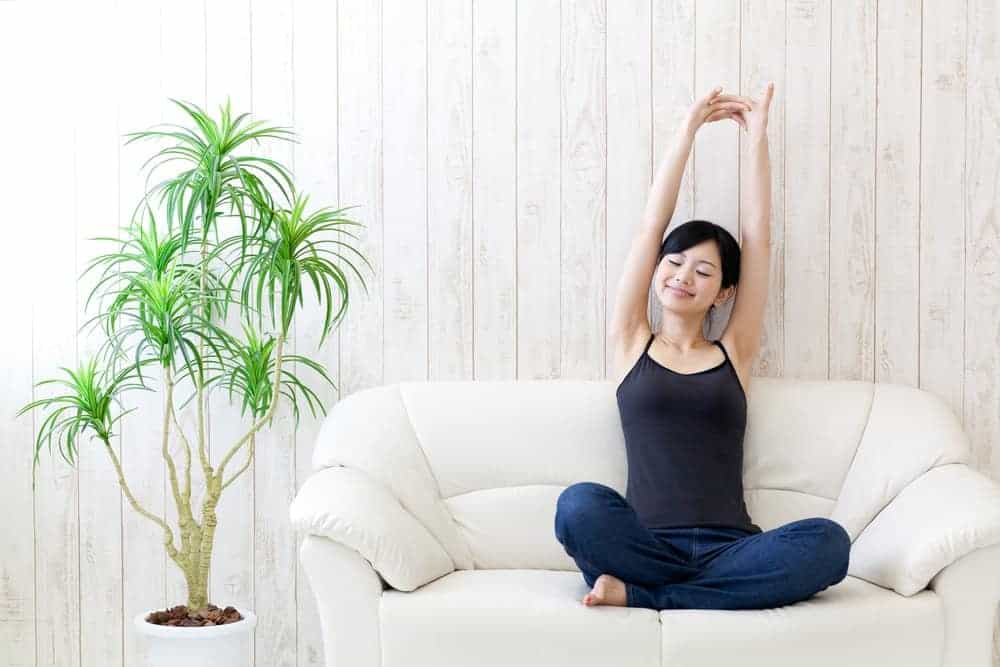 A woman wearing comfortable camisoles while relaxing on the couch.