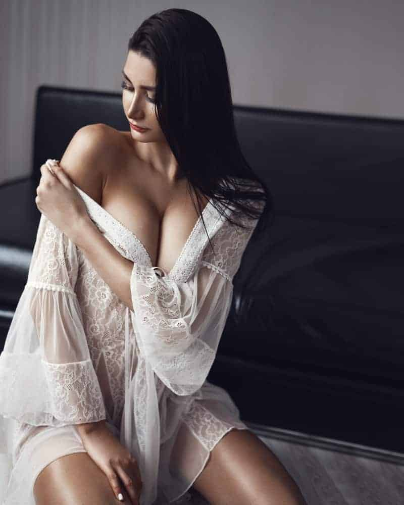 A woman putting on a white lace chemise.