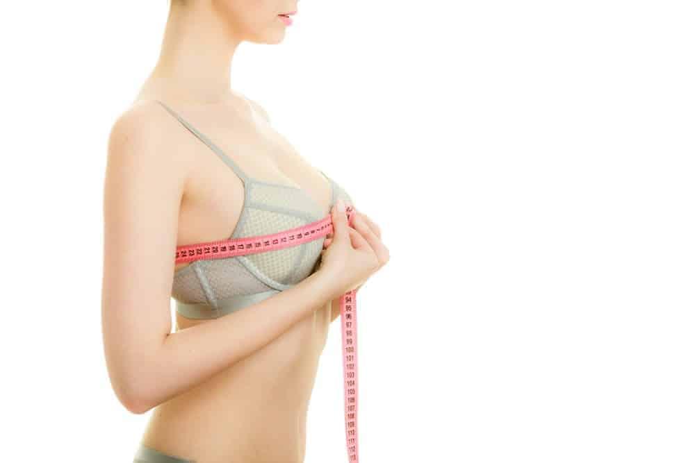 A woman wearing a bra measuring her bust.