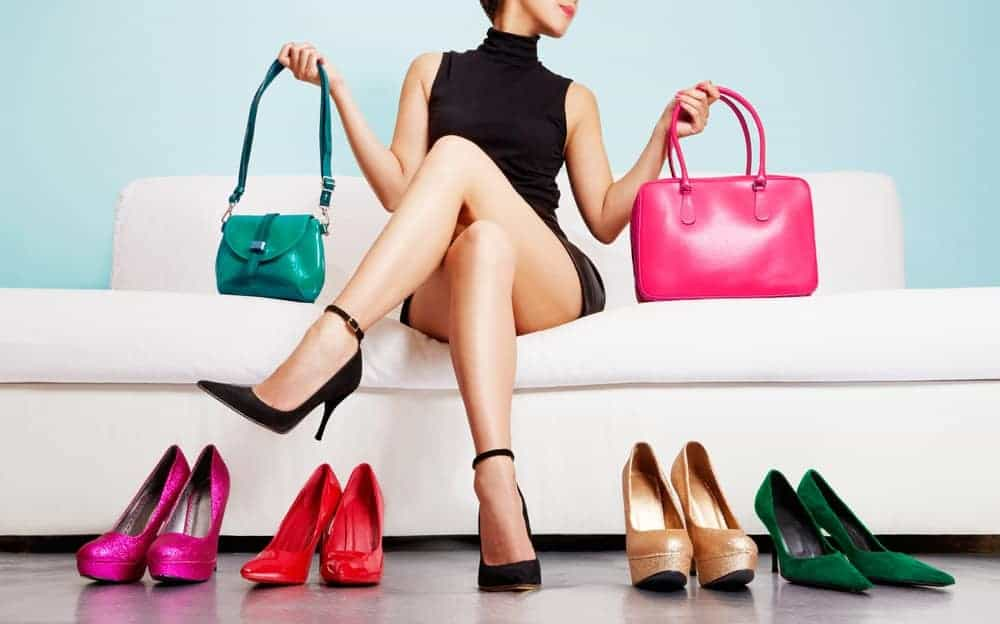 A woman sitting on a couch with her bags and shoes on display.