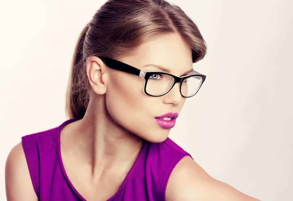 A woman wearing a pair of glasses with her makeup that matches her blouse.