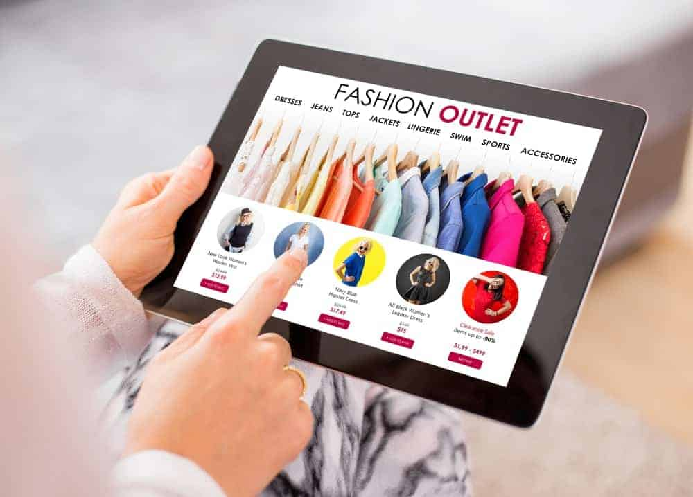 A woman shopping clothes online with her tablet.