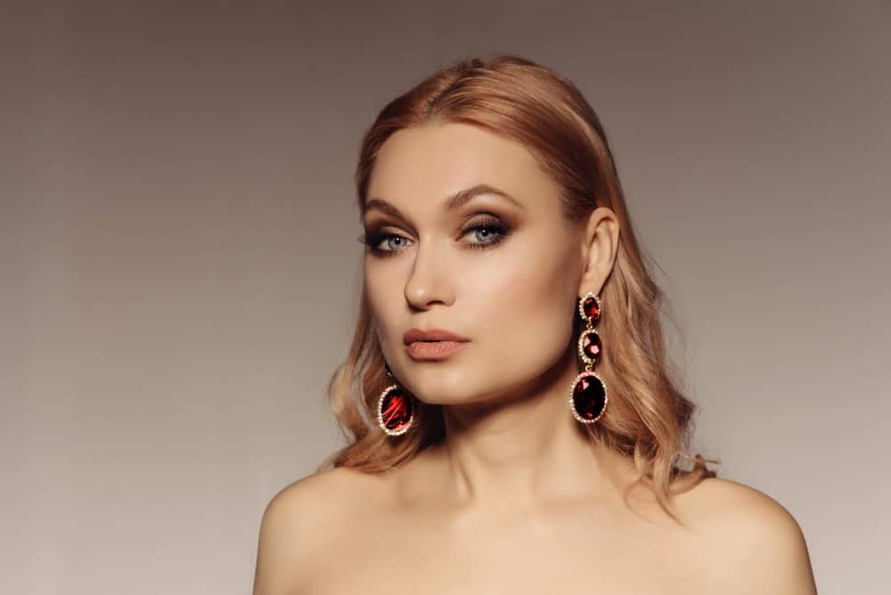 A blonde woman wearing a pair of ruby statement earrings.