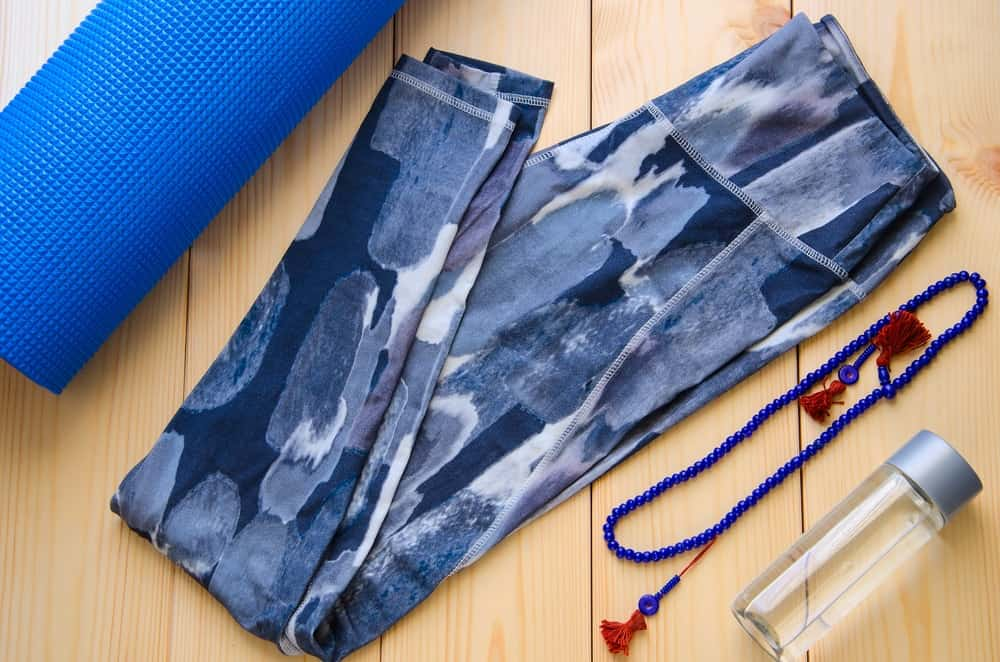 A look at a pair of yoga pants, a yoga mat and a water bottle.