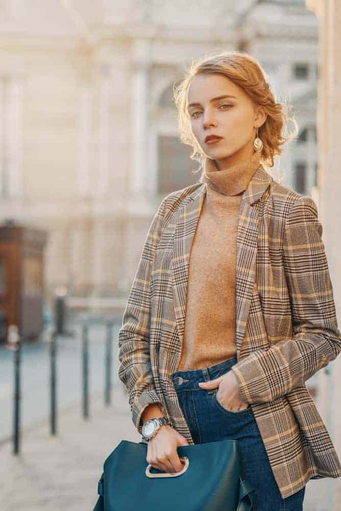 A woman wearing a pair of jeans with her plaid jacket.