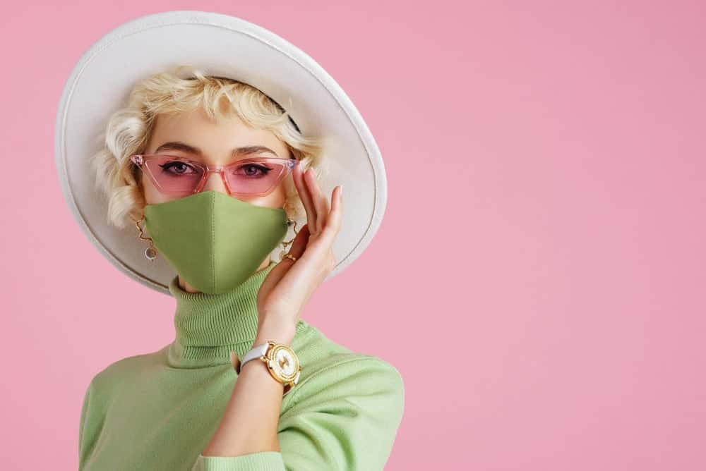 A stylish woman wearing a green turtleneck with her green mask.