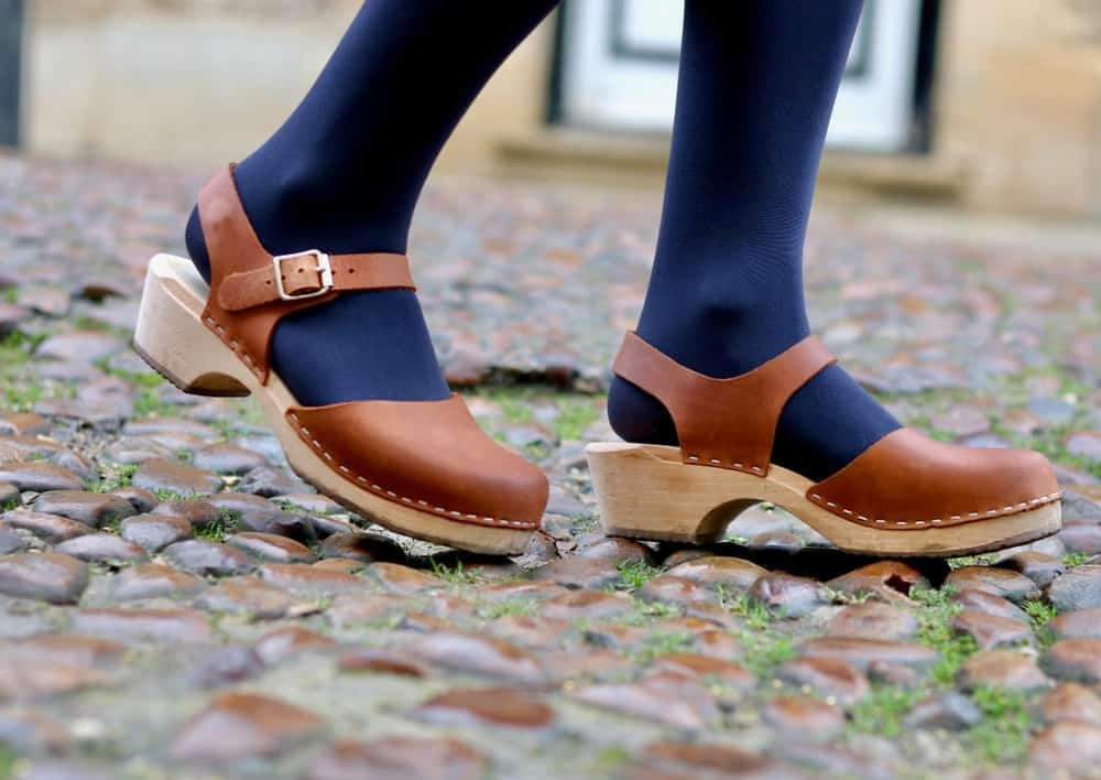 A woman walking on the cobblestones wearing wooden clog shoes with leather straps.