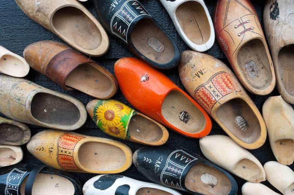 Various wooden clog shoes with different colorful designs.