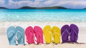 A row of colorful flip flops on a sandy beach.