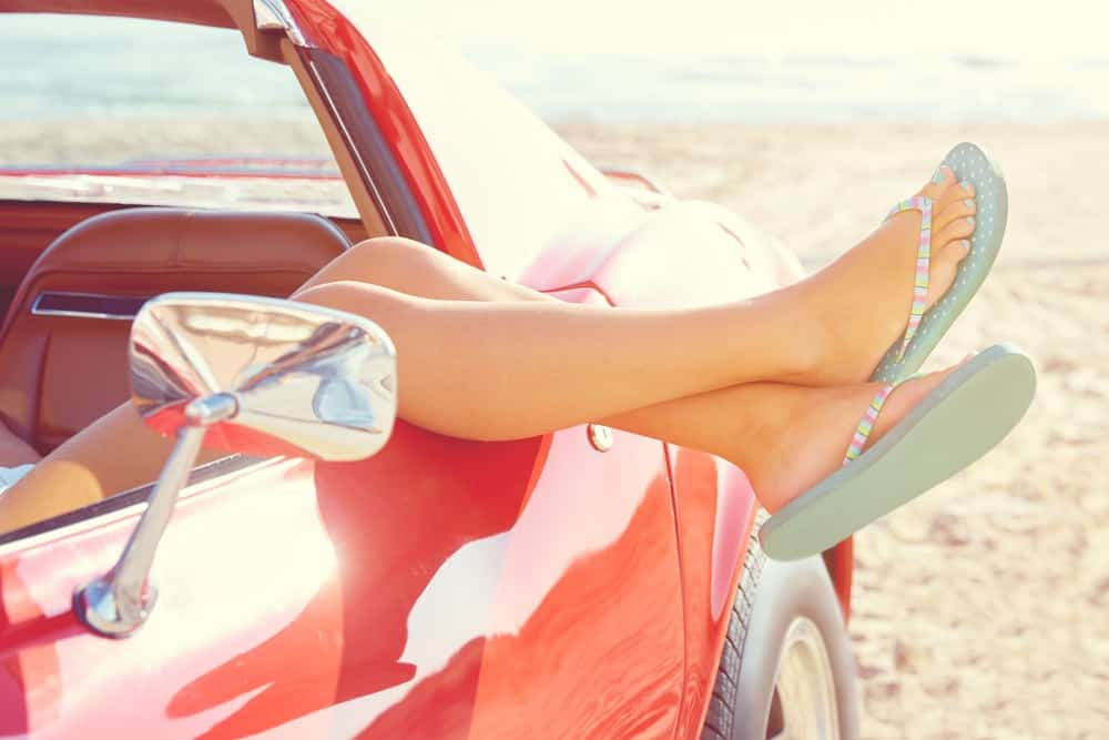 A woman wearing flip flops relaxing on a red car at the beach.
