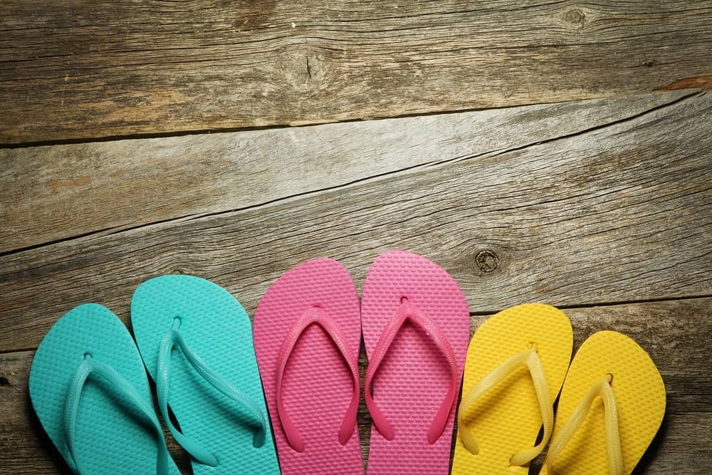 Pairs of colorful flip flops on a wooden floor.