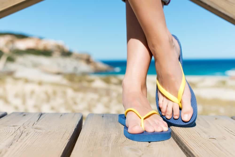 A woman wearing flip flops on a wooden deck overlooking the beach.