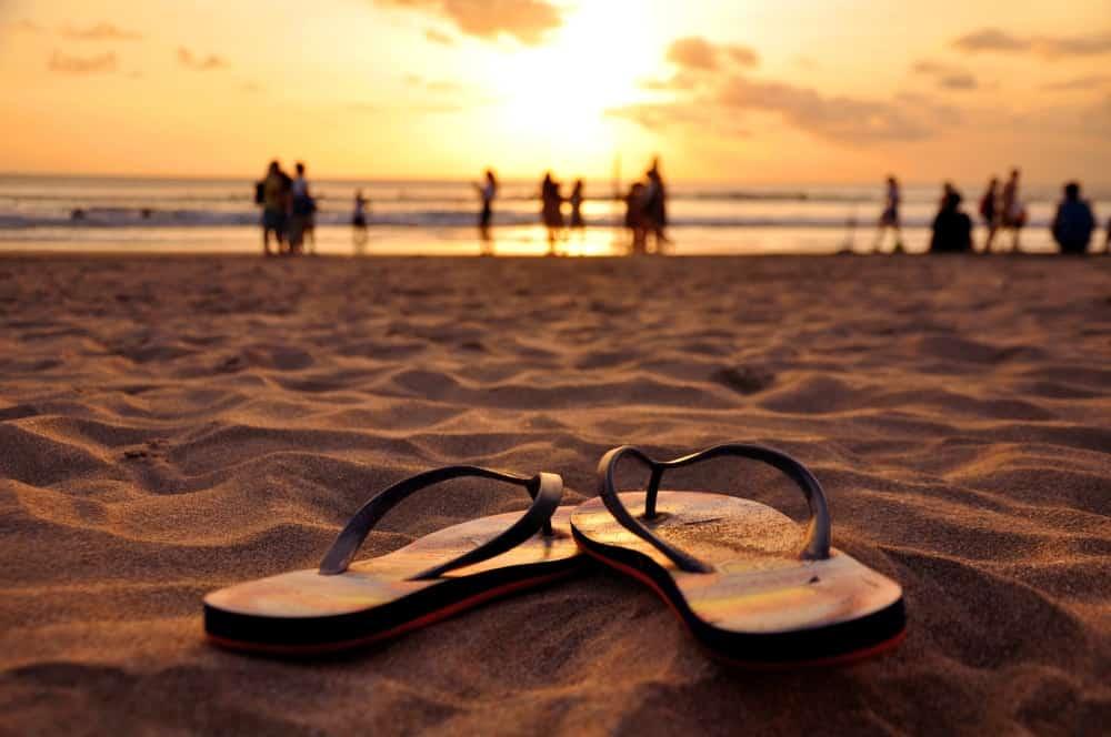 A pair of flip flops on a sandy beach at sunset.