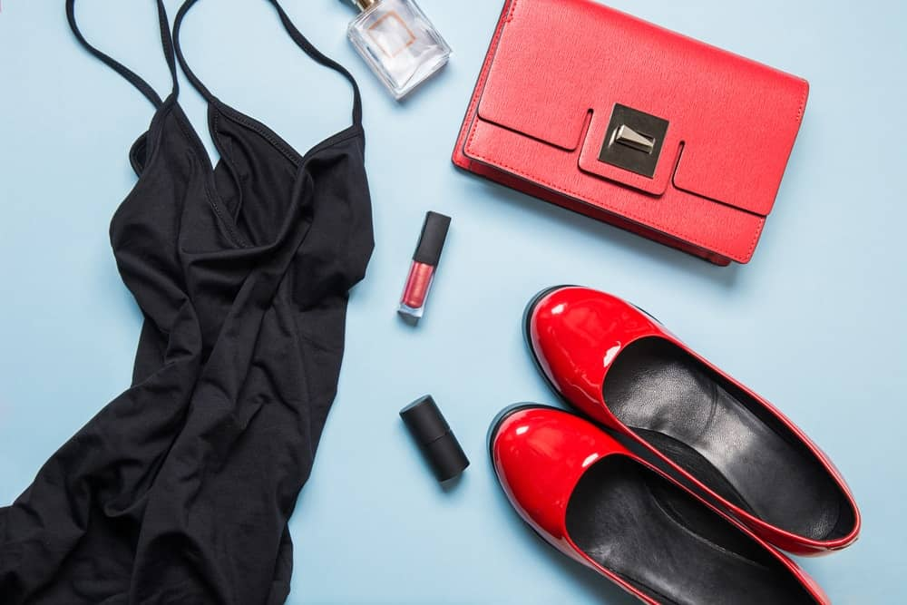 A close look at an outfit set with red accessories, red shoes and a little black dress.