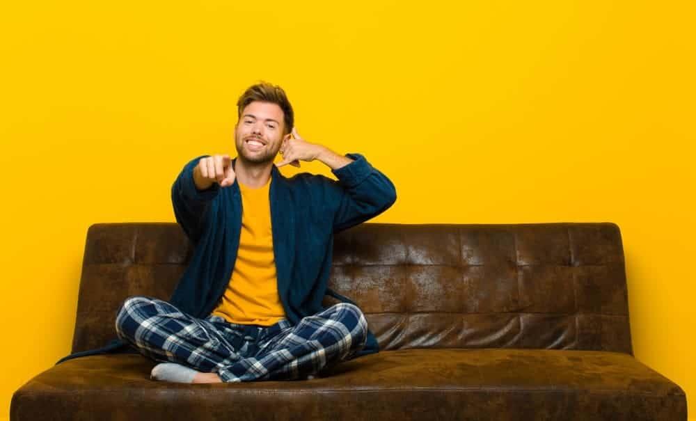 A man wearing loungewear on the sofa.